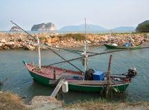 Il vecchio peschereccio è messo in bacino sui precedenti delle rocce della riva Fotografia Stock