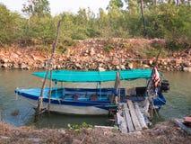 Il vecchio peschereccio è messo in bacino sui precedenti delle rocce della riva Fotografie Stock Libere da Diritti