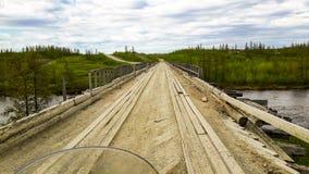 Il vecchio ponte di legno sopra un certo fiume in Siberia immagine stock