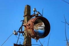 Il vecchio proiettore arrugginito ha montato su un supporto delle trasmissioni dell'elettricità fotografie stock libere da diritti