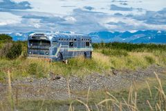 Il vecchio retro bus abbandonato si siede avanti in una palude lungo Homer Spit nell'Alaska fotografia stock libera da diritti