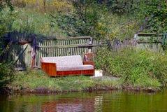 Il vecchio sofà vicino ad un di legno recinta l'erba sulla riva del lago Fotografia Stock