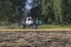 il vecchio trattore ara un campo dopo la raccolta del grano Fotografia Stock Libera da Diritti