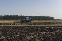 Il vecchio trattore ara un campo dopo la raccolta del grano 6 Immagini Stock
