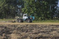 Il vecchio trattore ara un campo dopo la raccolta del grano 4 Fotografia Stock