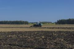 Il vecchio trattore ara un campo dopo la raccolta del grano 3 Fotografia Stock Libera da Diritti