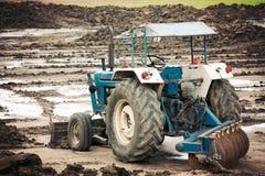 Il vecchio trattore nella costruzione sta regolando la terra Fotografia Stock