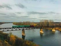Il vecchio treno attraversa il fiume sul ponte fotografie stock libere da diritti