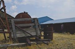 Il vecchio vagone di legno sulla vecchia azienda agricola arrugginita fotografie stock