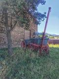 Il vecchio vagone si siede da un granaio di pietra Immagini Stock