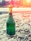 Il vecchio verde bottiglia del vino si trova sul lungomare nella sabbia Immagine Stock