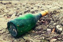 Il vecchio verde bottiglia del vino si trova sul lungomare nella sabbia Fotografia Stock