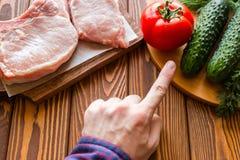 Il vegetariano dell'uomo sceglie la carne delle verdure invece Fotografie Stock
