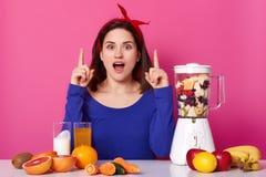Il vegetariano moro creativo ispirato ha idea di nuovo modo di cottura, bastoni alla dieta sana, andante bere la frutta nutriente fotografie stock