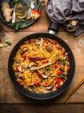 Il vegetariano saporito ha fritto la pentola delle tagliatelle con le verdure e la salsa di pasta cremosa su fondo di legno fotografia stock libera da diritti