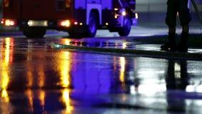 Il veicolo del pompiere che pulisce la via alla notte video d archivio