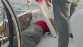 Il veleggiatore in uniforme di rosso è all'armadio posteriore che ripara il collegamento della macchina della direzione dell'yach video d archivio