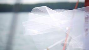 Il velo nuziale trasparente bianco ondeggia in aria sul lago stock footage