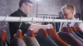 Il venditore aiuta un giovane uomo elegante a scegliere un vestito classico nel deposito video d archivio