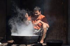 Il venditore ambulante indiano rende ad alimenti a rapida preparazione in vecchio wok il fuoco Pushkar, India Fotografie Stock