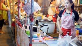 Il venditore asiatico della donna prepara l'alimento e la vendita sul mercato di notte della via thailand archivi video