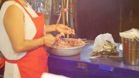 Il venditore asiatico della donna versa la carne fresca su un kebab Jomtien, Tailandia Pattaya video d archivio
