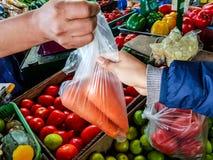 Il venditore che consegna alcune carote al cliente immagini stock