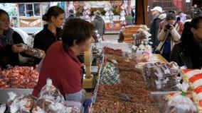 Il venditore della donna in una tenda con alimento parla con clienti al festival di Oktoberfest Monaco di Baviera, Germania video d archivio