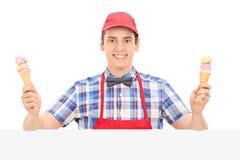 Il venditore maschio che tiene due gelato dietro un pannello Immagini Stock Libere da Diritti