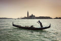 Il Veneziano. A gondolier in the foreground with a cathedral in the background royalty free stock photography