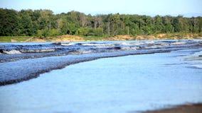 Il vento guida le onde sul fiume, il lago, onde su una spiaggia sabbiosa stock footage