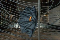 Il vento rotto soffiato ha danneggiato l'ombrello su un recinto Immagine Stock