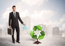 Il verde d'innaffiatura dell'uomo di affari ricicla l'albero del segno sul fondo della città Fotografia Stock
