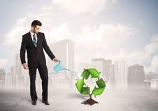 Il verde d'innaffiatura dell'uomo di affari ricicla l'albero del segno sul fondo della città Immagini Stock