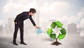 Il verde d'innaffiatura dell'uomo di affari ricicla l'albero del segno sul fondo della città Fotografia Stock Libera da Diritti