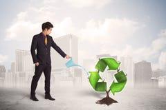 Il verde d'innaffiatura dell'uomo di affari ricicla l'albero del segno sul fondo della città Fotografie Stock