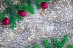 Il verde dell'albero di Natale si ramifica, palle rosse, woode isolato dalla neve dell'inverno Immagini Stock