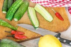 Il verde fresco ha affettato i cetrioli, i peperoncini rossi, limone sul tagliere di legno della cucina Cottura dell'insalata di  immagini stock libere da diritti