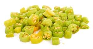 Il verde fresco ha tagliato i pezzi del peperoncino su un fondo bianco immagine stock