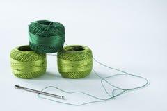 Il verde lavora all'uncinetto il filato con le forbici e l'ago Fondo bianco, fotografia stock
