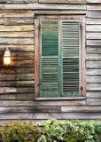 Il verde shutters la finestra eccessiva chiusa con la luce del portico Immagini Stock