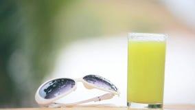 Il versamento del vetro del succo del kiwi che crea la spruzzata ha messo il fiore del frangipane accanto agli occhiali da sole s archivi video
