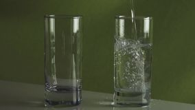 Il versamento spruzzando l'acqua nel movimento lento di vetro immagazzina il video del metraggio video d archivio