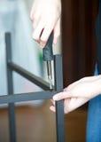 Il verticale delle mani avvita insieme un pezzo di mobili metallici Immagini Stock