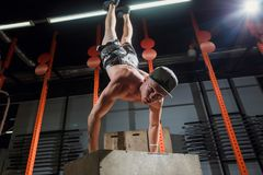 Il verticale sull'uomo che di flessione della scatola l'allenamento alla palestra spinge aumenta Fotografia Stock