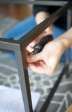 Il verticale vicino su delle mani che avvitano insieme i mobili metallici collega fotografia stock libera da diritti