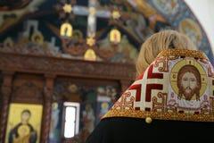 Il vescovo ortodosso sta pregando davanti all'altare Immagine Stock