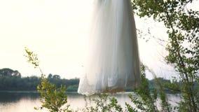 Il vestito bianco da nozze appende su un albero video d archivio