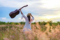 Il vestito bianco dalle donne di stile di vita che tiene una chitarra su un tramonto o su un cielo nuvoloso dell'alba nel fiore d fotografia stock libera da diritti