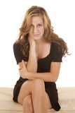 Il vestito dal nero della donna si siede affrontando le gambe trasversali serie fotografia stock